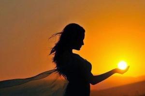 femme-voile-tient-soleil-main-ombre-orangee